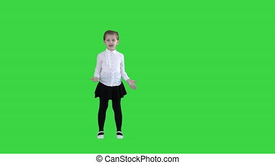 Cute little girl smiling and confidently talking to camera on a Green Screen, Chroma Key.