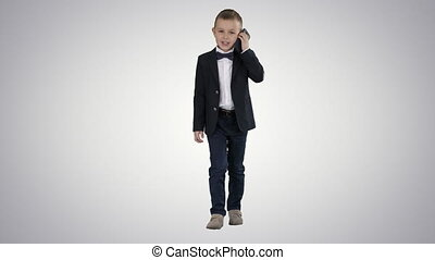 Little boy in a costume making a phone call while walking on gradient background.