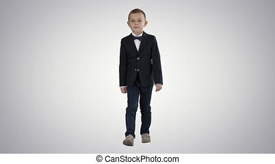 Little boy in a costume with a bow tie walking on gradient background.