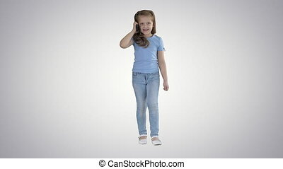 Little cute girl making a phone call while walking on gradient background.