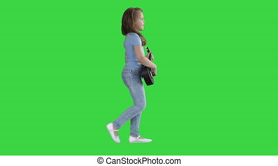 Cute little girl walking and singing while playing on ukulele on a Green Screen, Chroma Key.