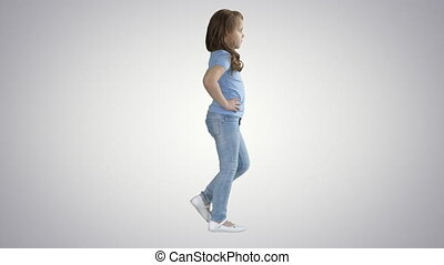 Little girl in casual clothes walking on gradient...
