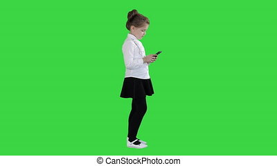 Little Girl Using Cell Smart Phone on a Green Screen, Chroma...
