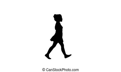 Full lenght shot. Side view. Silhouette Little girl in school uniform walking by. Professional shot in 4K resolution. 016. You can use it e.g. in your commercial video, education, business, presentation, broadcast
