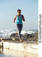 Full length African american woman running by the sea