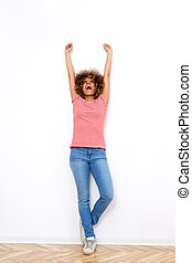 Full length african american woman smiling with arms raised