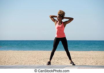 Full length afro american female exercising at beach