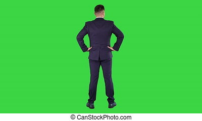 Businessman looking around with hands on hips on a Green...