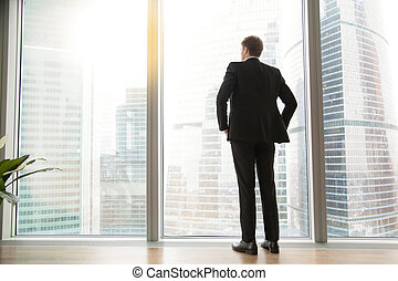 Full length back view of successful businessman in big city