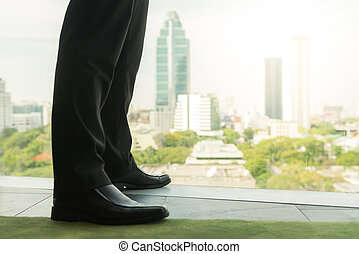 Full length back view of successful businessman in suit standing in office with hands on his waist, CEO looking through window at big city buildings, planning new project, waiting for meeting to start