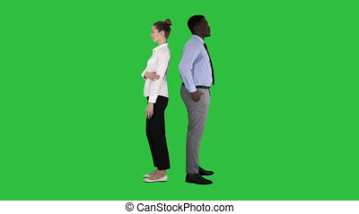 Beautiful and handsome guy standing back to back changing poses on a Green Screen, Chroma Key.