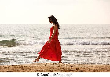 Full length beautiful woman in red dress walking alone on beach