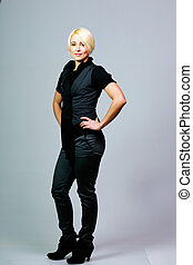 Full-length beautiful woman standing on gray background