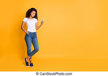 Full length body size photo of cheerful confident positive nice charming beautiful girl curly wavy wearing white t-shirt jeans denim footwear with hand pocket isolated over vivid color background