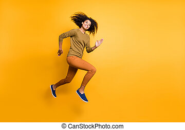 Full length body size photo of cheerful positive beautiful attractive charming pretty girl wearing orange pants trousers running jumping towards empty space isolated over vivid color background