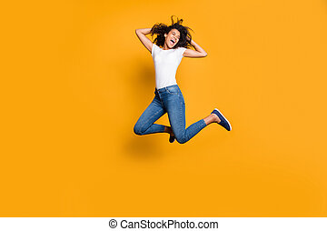 Full length body size photo of cheerful positive cute nice pretty girl jumping up high wearing jeans denim white t-shirt isolated over vivid color background