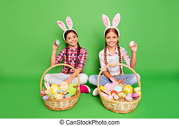 Full length body size photo of lovely cheerful excited glad nice carefree having free time charming long haired schoolgirls sitting resting floor holding painted eggs isolated bright vivid background