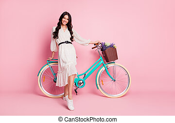 Full length body size photo of pretty girl standing with blue bicycle on holidays isolated on pastel pink color background