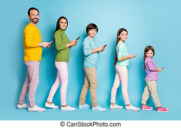 Full length body size profile side view of nice attractive glad cheerful big full family pre-teen kids using 5g device reading post walking isolated on bright vivid shine vibrant blue color background