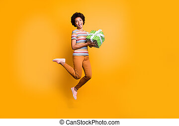 Full length body size turned photo of jumping girl holding giftbox with hands wearing pants trousers striped t-shirt footwear isolated over vivid yellow color background