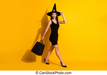 Full length body size view of her she attractive pretty cheerful cheery slender lady wizard carrying bags bargain going touching cone hat isolated bright vivid shine vibrant yellow color background