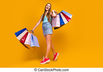 Full length body size view of her she nice attractive lovely pretty cheerful cheery straight-haired girl carrying new things isolated on bright vivid shine vibrant yellow color background