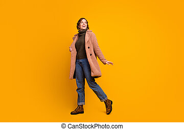 Full length body size view of her she nice attractive lovely pretty fashionable cheerful cheery girl strolling spending weekend isolated over bright vivid shine vibrant yellow color background