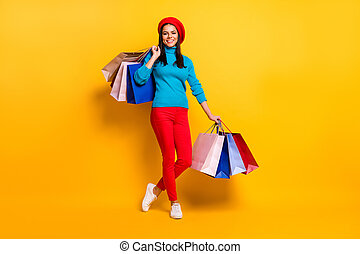 Full length body size view of her she nice attractive lovely pretty trendy cheerful cheery fashionable girl having fun carrying bargains isolated on bright vivid shine vibrant yellow color background