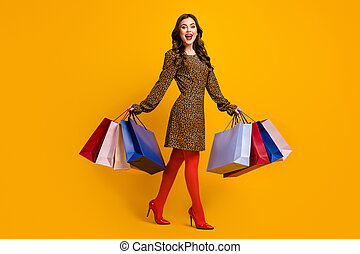 Full length body size view of her she nice attractive pretty charming cheerful wavy-haired girl carrying bags new things walking isolated on bright vivid shine vibrant yellow color background