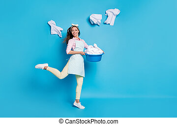 Full length body size view of her she nice attractive pretty cheerful cheery maid jumping going carrying laundry neat tidy cleanup isolated on bright vivid shine vibrant blue color background