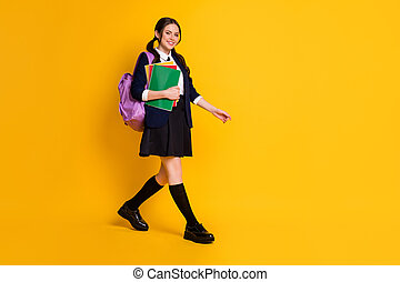 Full length body size view of her she nice attractive pretty cheerful schoolgirl going to secondary school carrying literature isolated on bright vivid shine vibrant yellow color background