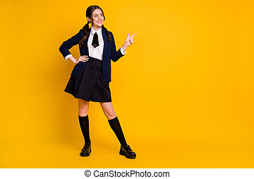Full length body size view of her she nice attractive pretty glad cheerful cheery schoolgirl demonstrating copy space select advert ad isolated on bright vivid shine vibrant yellow color background