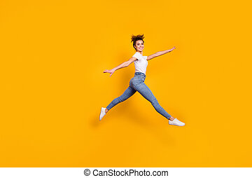 Full length body size view of her she nice attractive pretty sporty feminine graceful slender cheerful girl jumping running going walking isolated on bright vivid shine vibrant yellow color background