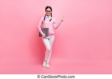 Full length body size view of her she nice cheerful confident brown-haired teenage girl holding in hand laptop demonstrating copy space advert learn study isolated pink pastel color background
