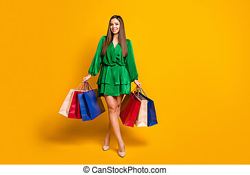 Full length body size view of her she nice-looking attractive lovely pretty cheerful cheery straight-haired girl carrying new things isolated over bright vivid shine vibrant yellow color background