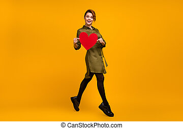 Full length body size view of her she nice-looking attractive lovely pretty lovable cheerful cheery girl going holding in hand red heart isolated on bright vivid shine vibrant yellow color background