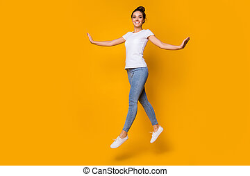 Full length body size view of her she nice-looking attractive lovely pretty winsome cheerful cheery girl jumping walking isolated over bright vivid shine vibrant yellow color background