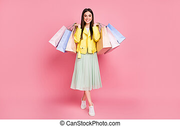 Full length body size view of her she nice-looking attractive pretty fashionable cheerful cheery girl carrying new things goods isolated on bright vivid shine vibrant yellow color background