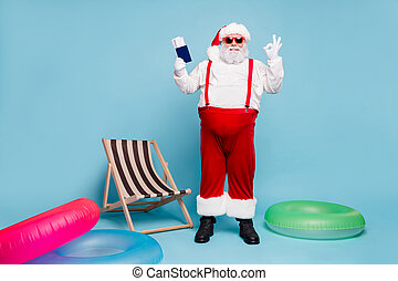 Full length body size view of nice cheerful fat big belly bearded Santa holding in hands passport tickets showing ok-sign isolated on blue turquoise pastel color background