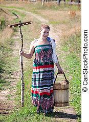 Full-length brunette in sundress on country road with rakes