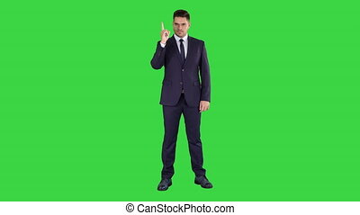 Business man pointing up finger making an accent on a Green Screen, Chroma Key.