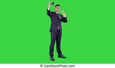 Business man taking selfie on a Green Screen, Chroma Key. -...