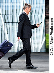Full length business man walking with suitcase and mobile phone