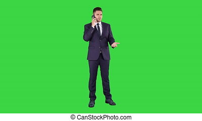 Business, technology and people concept - smiling businessman with smartphone talking on a Green Screen, Chroma Key.