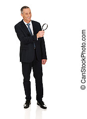Full length businessman with a magnifying glass