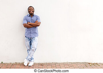 Full length cool young african man leaning against white wall and smiling