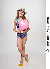 Full length girl in swimsuit and summer hat with pink...