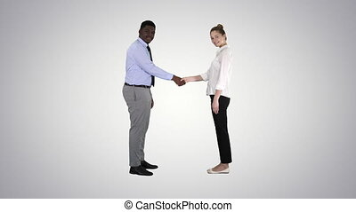 Handshake of business woman and business man posing for the picture on gradient background.