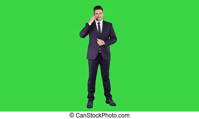 Handsome businessman with headset looking into camera and smiling on a Green Screen, Chroma Key.