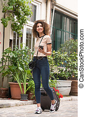 Full length happy african american woman walking on street with suitcase and mobile phone